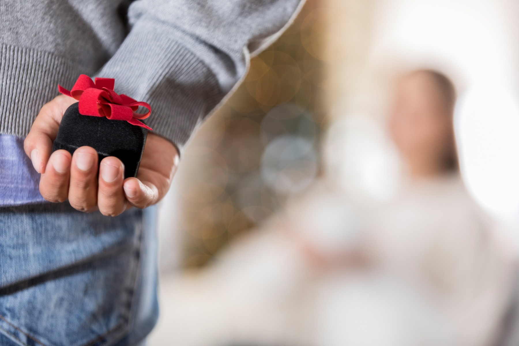 Man holding ring box behind his back ahead of marriage proposal